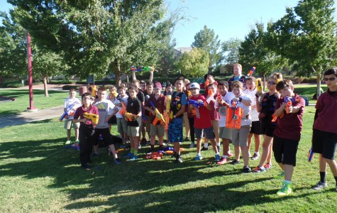 Nerf Club members meet at the park behind Faith ready for action. Many kids have their guns locked and loaded, and are ready to fire their guns at will.