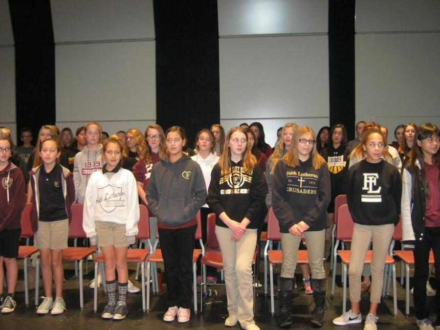 Faith Lutheran's middle school choir practicing for the concert on December eleventh. They are all practicing the three songs they will be performing.