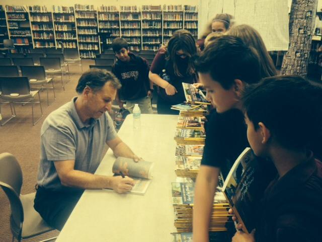 Mike Graf signing books when he visited on November 13. Students are going to get the chance to write their own book in January.
