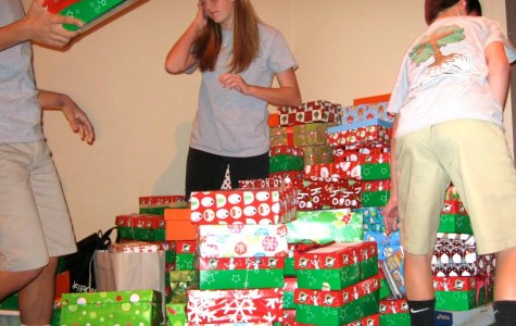 Joanne Krafft's applied class stacks Operation Christmas Child boxes on the stage. Any contribution to this organization can help anyone this Christmas
