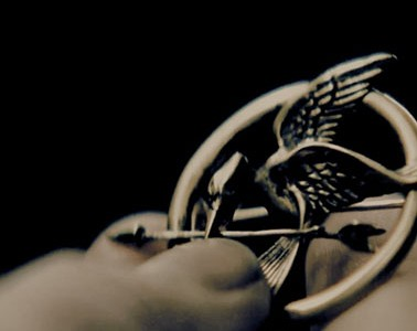 "Katniss holds her mockingjay pin close to her. ""Mockingjay Part 1"" made a profit of 275 million dollars, world-wide, and broke the record for the year's biggest domestic opening weekend. This film can be found at local retailers and online for purchases."