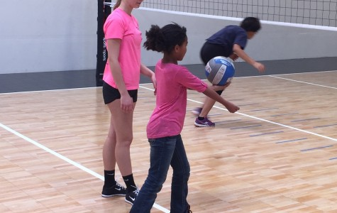 Faith Lutheran High School volleyball player helps a girl during camp learn how to underhand serve. All of the girls will later take part in scrimmages.