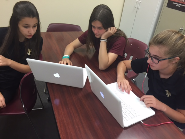 Students Nicola Talbot, Grace Balle, and Sara Short work on Aurasma and help plan for distributing. The yearbook class will distribute on May 29.