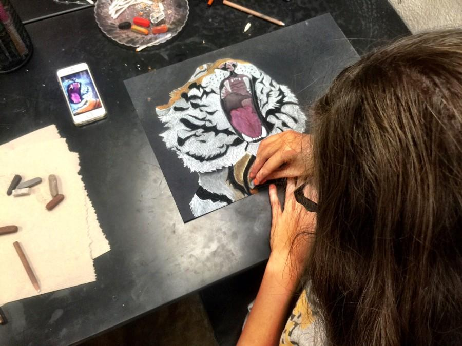 NJAHS student working on a art piece inspired from a photo of a tiger. NJAHS students learn the art skills they need to persue their passion in artistry.