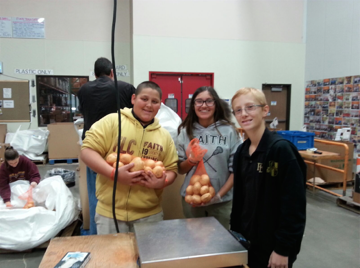Students Noah Mitchell, Cooper Davis, and Lisa Negrete help at last year's service event by packaging potatoes. The service event has grown with the expansion of students since it started in 2006.