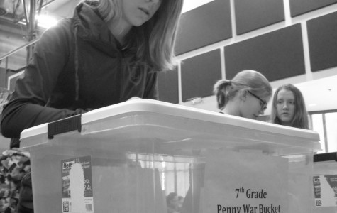 Seventh grader Kylie Harris puts money for the penny drive in her grade's box. This was a competition between the middle school grades during the first week of the Hearts 4 Jesus campaign at Faith Lutheran.