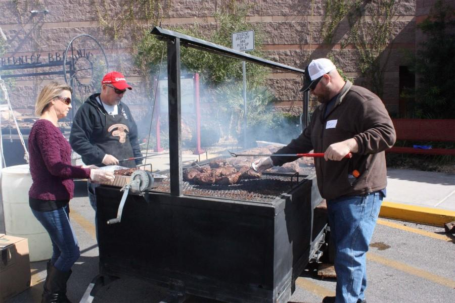 Two+of+the+volunteer+grillmasters+work+on+searing+steaks+to+perfection%2C+while+a+Faith+Lutheran+volunteer+helps+with+gathering+the+grilled+steaks.+Multiple+people+work+to+get+all+of+the+meals+ready+before+people+start+arriving.