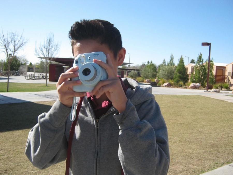 Evan Robinson takes a picture of his friends using the Instax Mini 8 by Fujifilm. This camera's small size makes it easier to travel with.