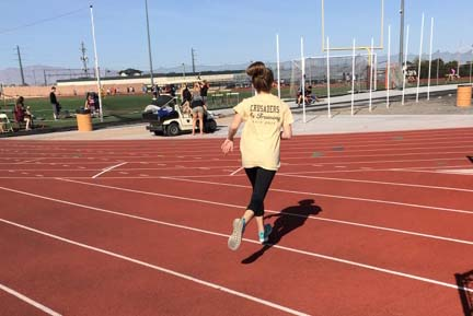 Seventh grader Isabella Lucente runs her two lap warmup during track. Track season occurs in spring, students practice everyday preparing for track meets, which occur almost every weekend.