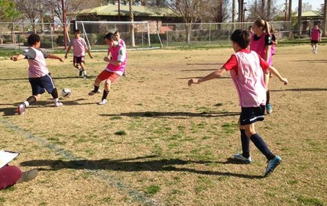 Two students battle for the ball, while others move around trying to help their teammate. Students worked hard at tryouts on March 14, 15, and 16 to show their skills to the coaches and earn their place on a team.
