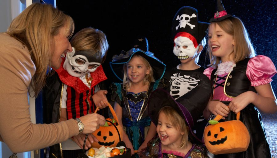 Courtesy of zliving.com  A woman hands out candy to a group of trick or treaters. This is a familiar scene that occurs in our community every year on Halloween.